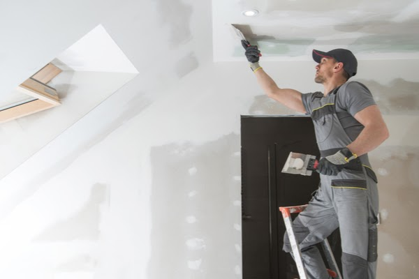 pro applying spackle to ceiling