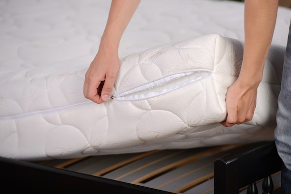 person putting mattress cover on bed
