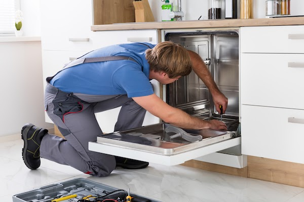 appliance repair specialist working on dishwasher