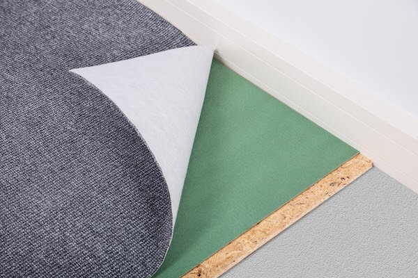 pulled back view of carpet to reveal underpad