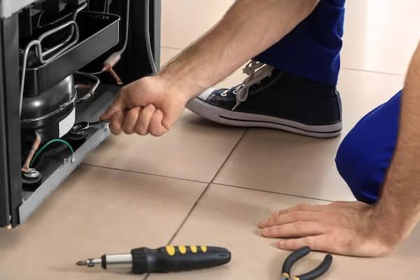 repairman fixing broken appliance