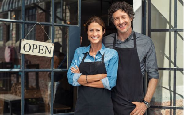 Two cheerful small business owners smiling and looking at camera while standing at entrance door. Happy mature man and mid woman at entrance of newly opened restaurant with open sign board.