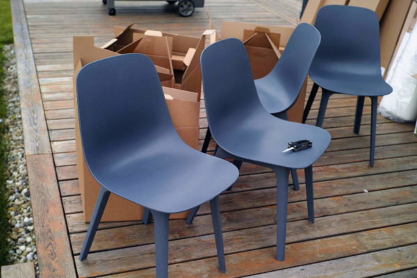 New plastic chairs assembling, a bunch of used cardboard boxes in the background, outdoor image