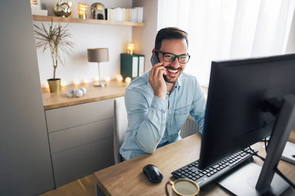 man on phone using computer in home office