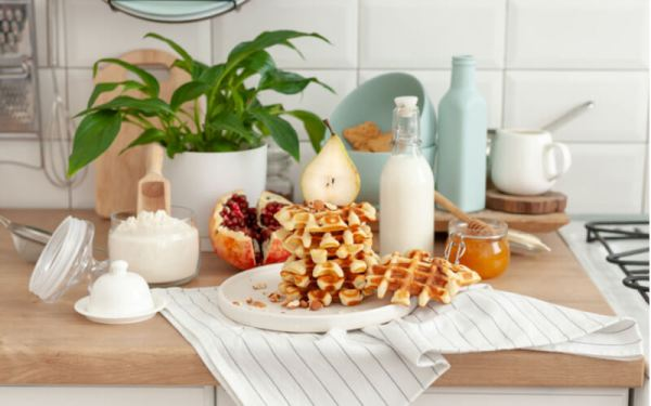 Cooked homemade waffles in the kitchen and the ingredients from which they are made