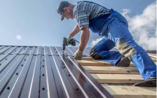 male builder performs work on the metal roof, fastens corrugated sheets
