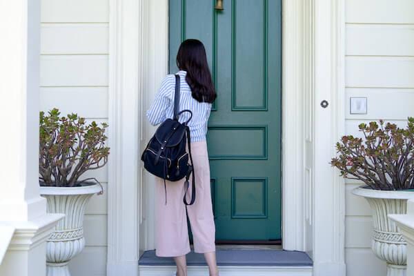 woman locking green front door of house