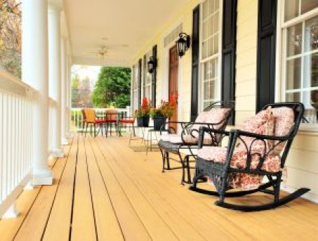 6249216 - low angle view of a large front porch with furniture and potted plants. vertical format.