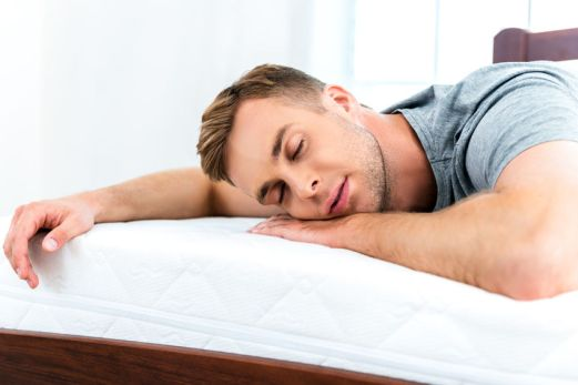 49654381 - photo of young man sleeping on nice white bed. young man demonstrating quality of mattress