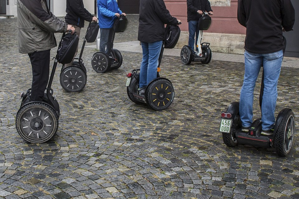a group of people on a segway tour, close up view of the segways and the peoples lower halves