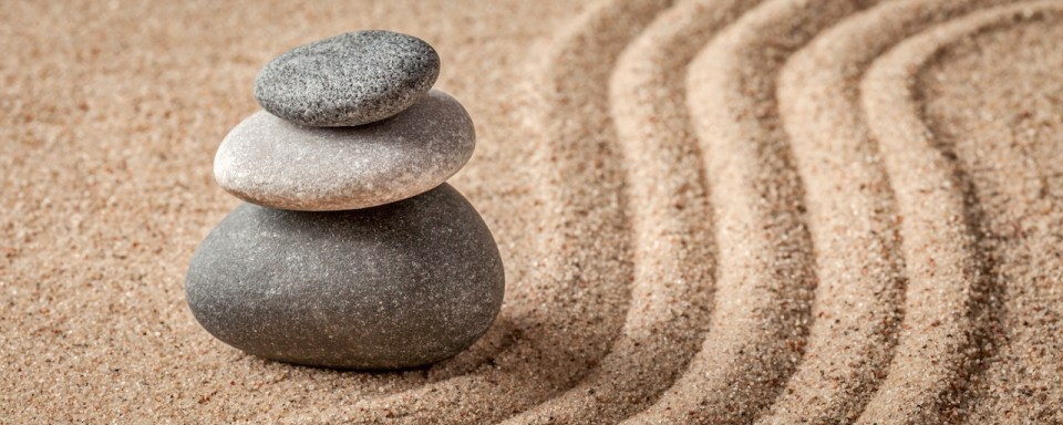Stacked rocks and lines raked through the sand in a Japanese Zen Garden