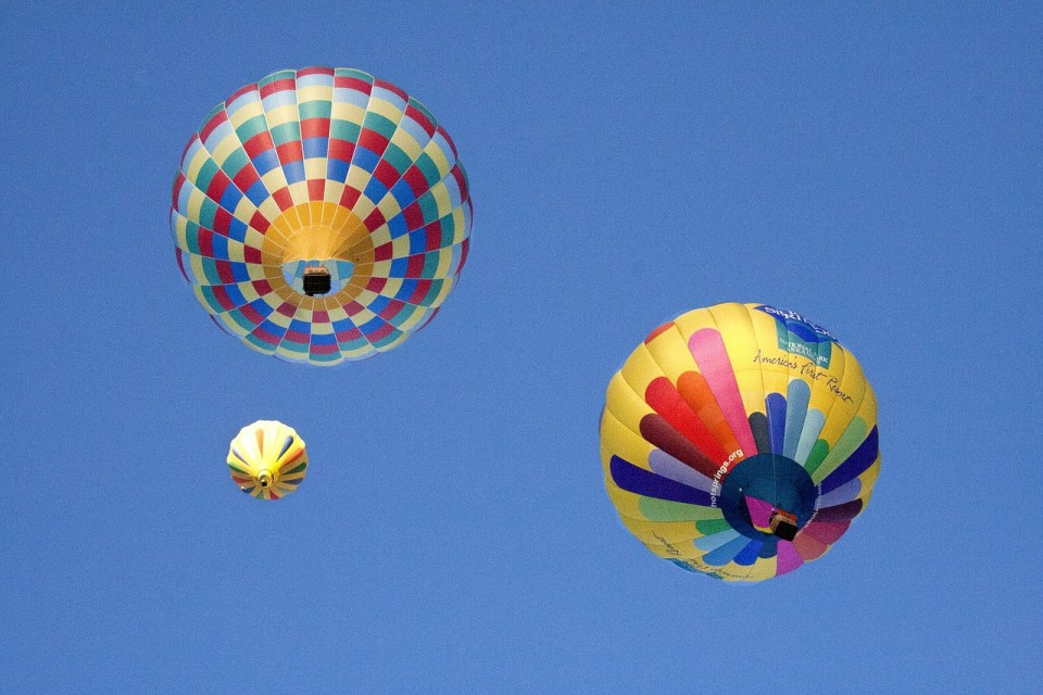three colorful hot air balloons in a clear blue sky
