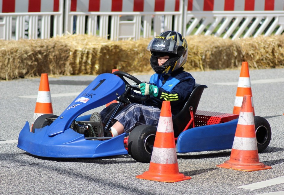 young boy getting ready to race in a go kart