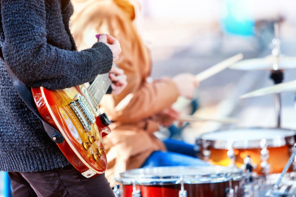 close up of street performers playing guitar and drums