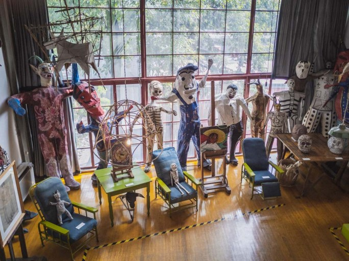A variety of multi colored life size puppets lean against a floor to ceiling glass window grid.