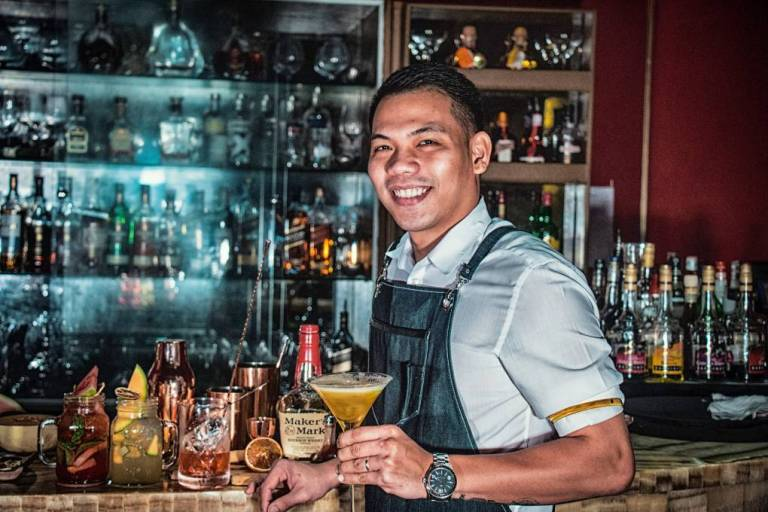 Friendly bartender holds a freshly mixed martini cocktail in Doha, Qatar.