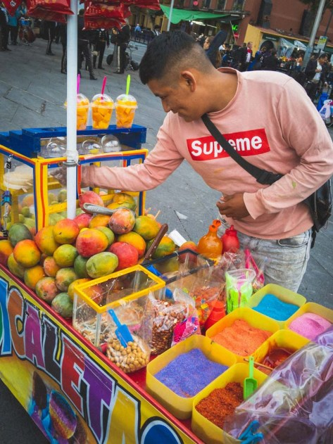 A bright yellow street cart filled with mangoes and a variety of brightly colored sugars is manned by a Mexican man in a long sleeved pink 'Supreme' T-shirt.