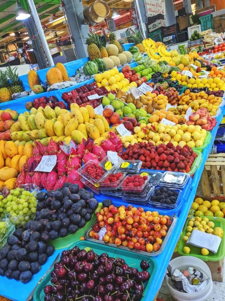 An overflowing market display of fresh tropical fruits including cherries, figs, mangoes, dragonfruit, grapes, and berries.