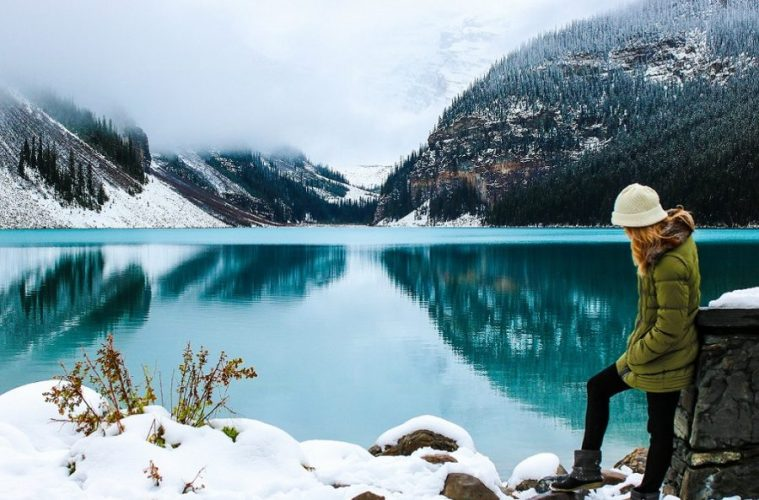 Woman standing beside placid lake surrounded by mountains during winter.