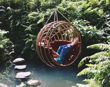 Woman lounging in hanging pod seat surrounded by foggy water, stepping stones and lush nature.