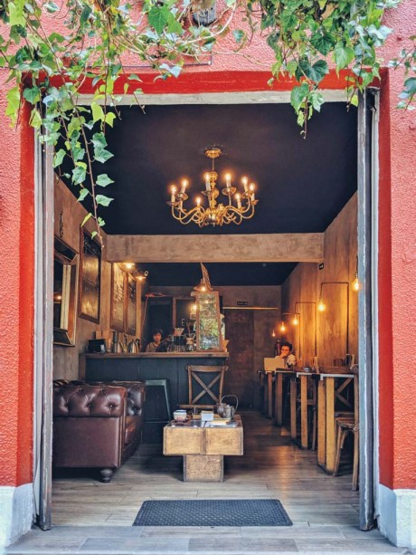A brown leather coach and a golden chandelier decorate a beautiful coffee shop interior.
