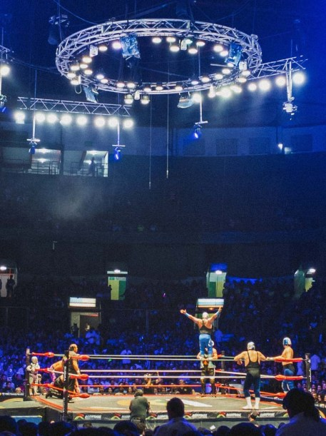 In a packed wrestling stadium, seven wrestlers occupy the ring and prepare for one wrestler to backflip off of the ropes.