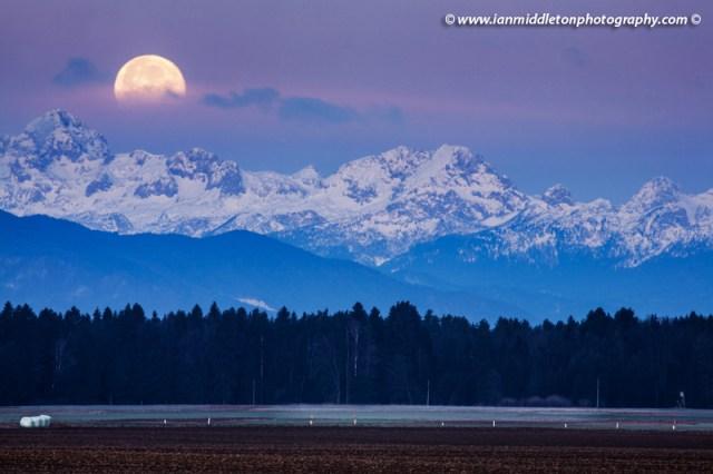 Full Moon setting over the Julian Alps in the morning, Brnik, Slovenia.