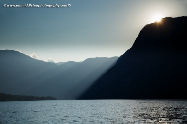 Light breaking as the sun passes over the mountains beside Lake Bohinj and produces sunrays over the lake, Triglav National Park, Slovenia.