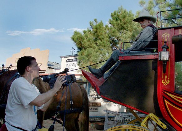 Giving direction to the stagecoach driver to speed up his entry.
