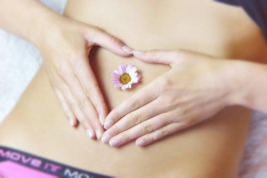 Mulher com as mãos em formato de coração sobre a barriga e com uma flor no centro.