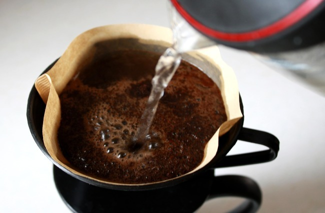 Café sendo passado dentro de um coador com filtro de papel, uma chaleira despeja água no pó de café.