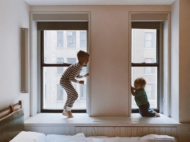 Duas crianças brincando perto das janelas de um apartamento.