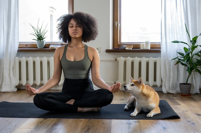 Mulher sentada no chão dentro de casa mostrando um exemplo de como meditar corretamente, ao seu lado está um cachorro.