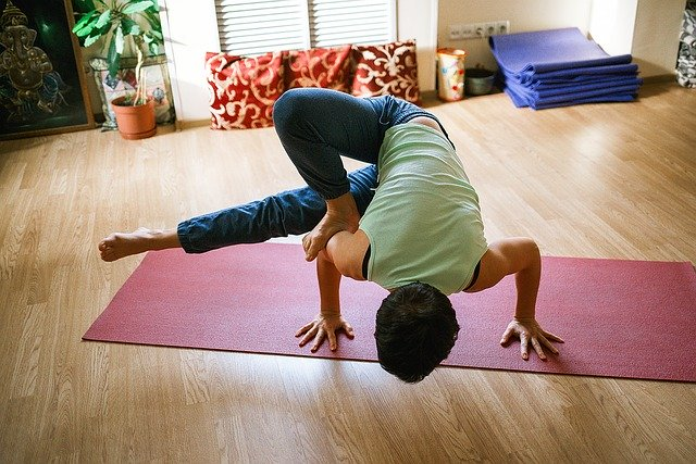 Pessoa se exercitando em casa após saber dos benefícios do yoga