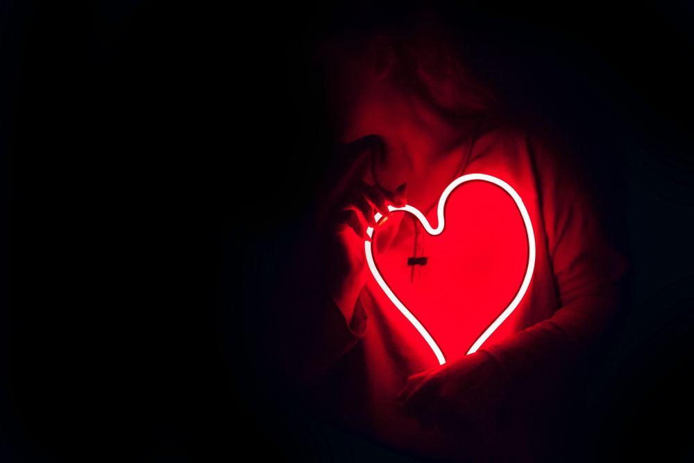 Pessoa no escuro segurando uma luminária em forma de coração.