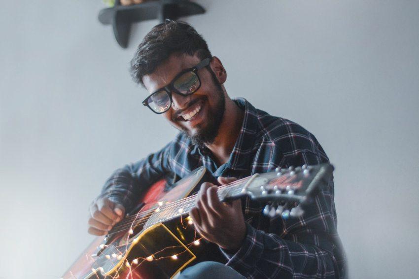Homem tocando violão, mostrando que o autocuidado pode estar em aprender novas habilidades.