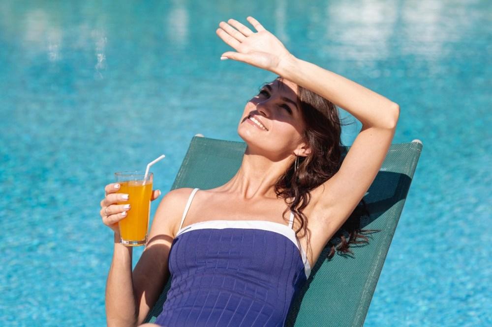 mulher tomando sol sem se preocupar com manchas de sol no rosto