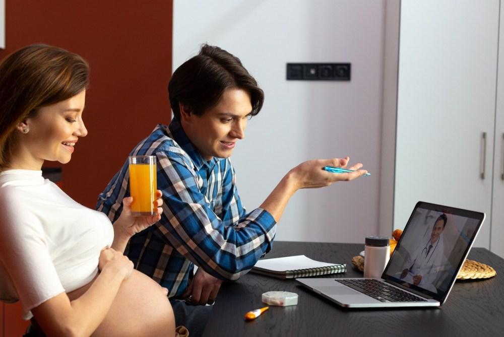 Uma mulher grávida e um homem estão contentes em uma chamada de vídeo com um médico através de um notebook.