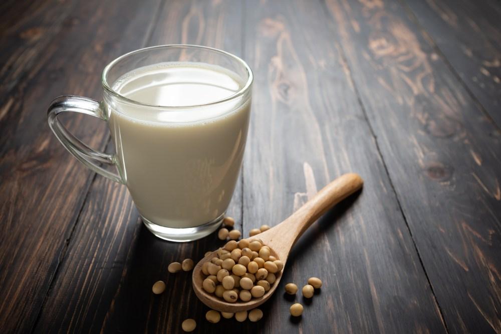 Uma xícara de leite com uma colher de soja ao lado.