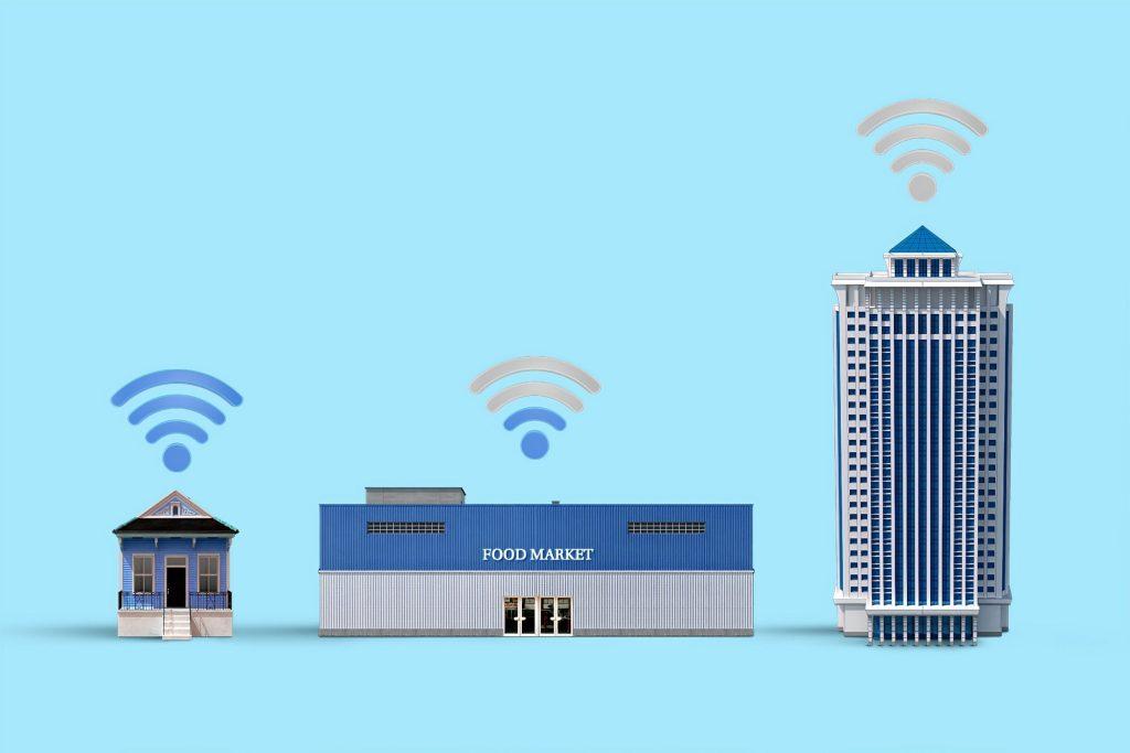 Desenho de uma casa, um mercado e um prédio, ilustrando que a IoT (internet das coisas) pode atuar em todos os setores.