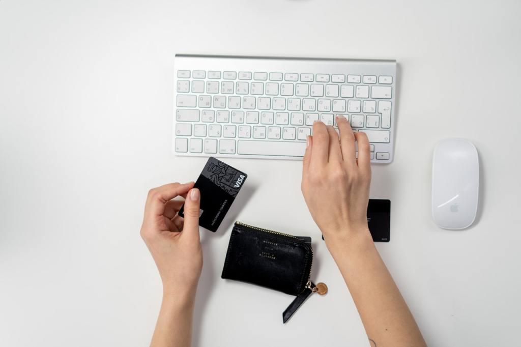 Pessoa digitando os dados de um cartão em um teclado, mostrando como acontecem as compras no varejo digital.