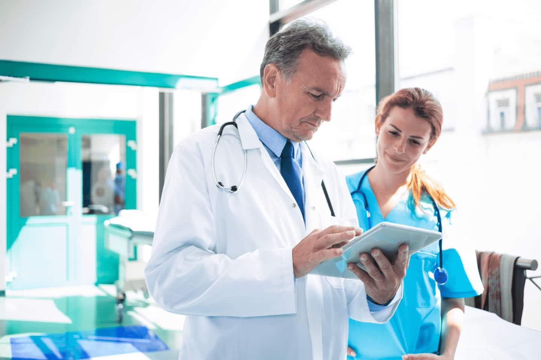 Foto de um médio e uma enfermeira, observando um tablet, dentro de um hospital, ilustrando o uso da automação e a importância do trabalho em conjunto da saúde e tecnologia.