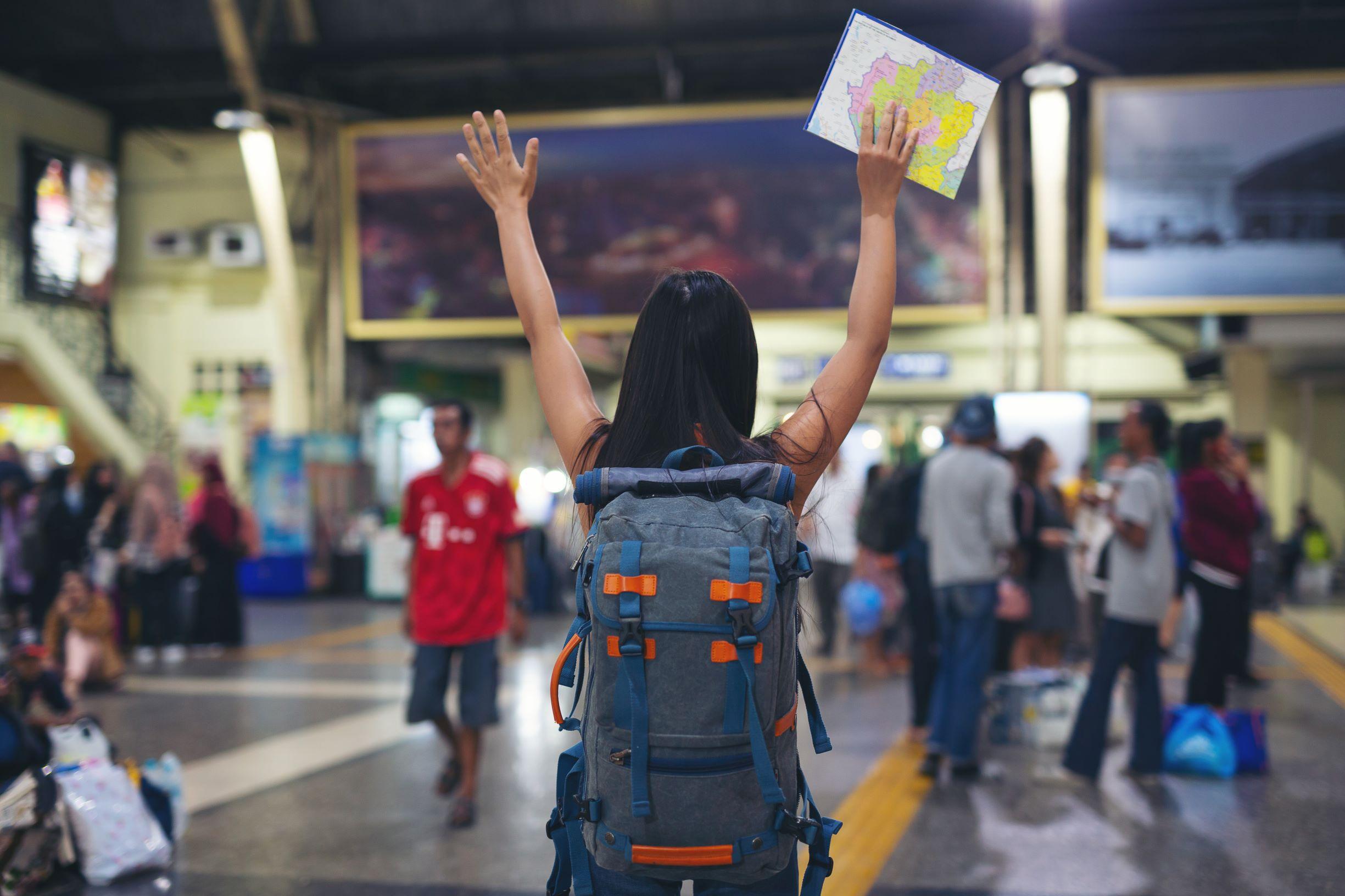 Foto de uma mulher de costas, com as mãos para o alto, segurando um mapa em uma das mãos e com uma mochila nas costas. A foto foi tirada em um aeroporto, demonstrando as múltiplas possibilidades de uma cidade digital.