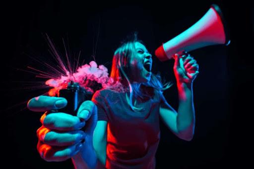 Mulher gritando em um megafone na sua mão esquerda e um sinalizador na mão direita