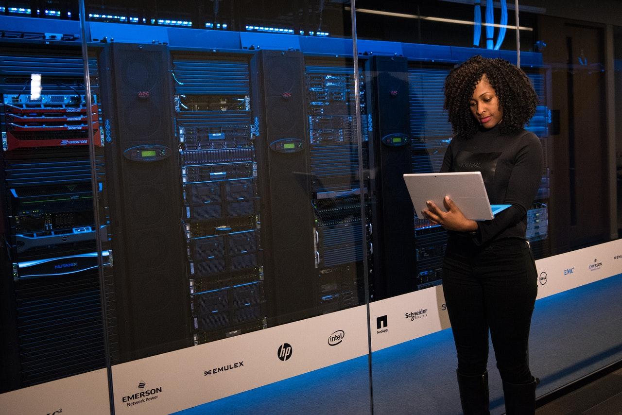 Mulher em pé segurando e olhando para ao notebook ao lado de um imenso servidor