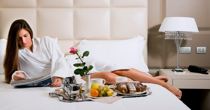 woman in hotel relaxing in luxury bathrobe