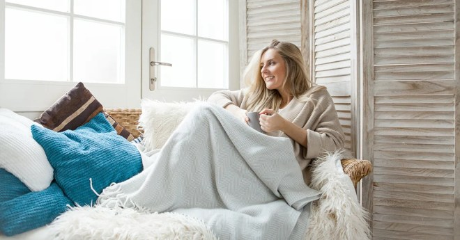 woman curled up in blanket at beach house