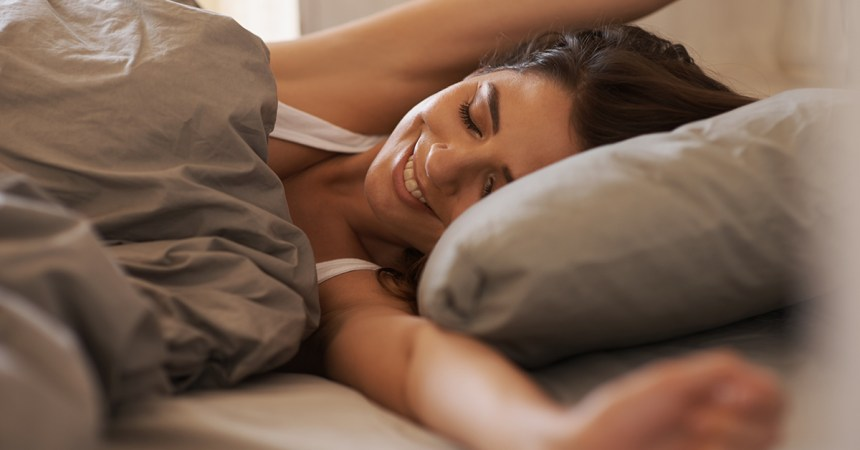Woman waking up at a bed and breakfast refreshed