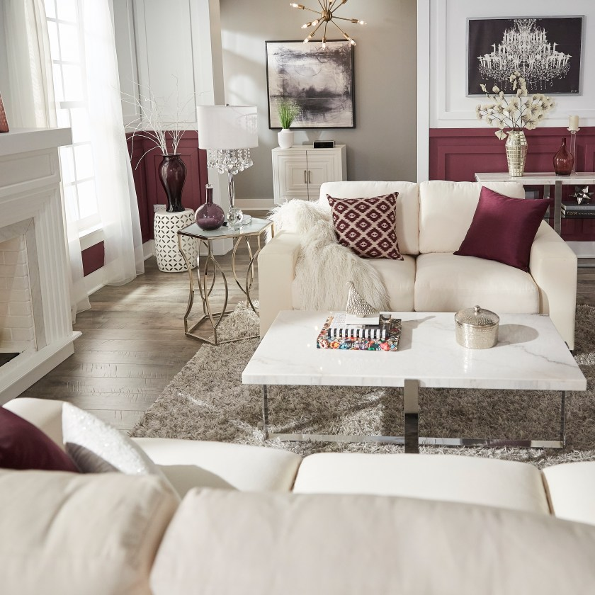 Glam designed living room with front view of white couch, purple pillows, marble cocktail table and glass end table