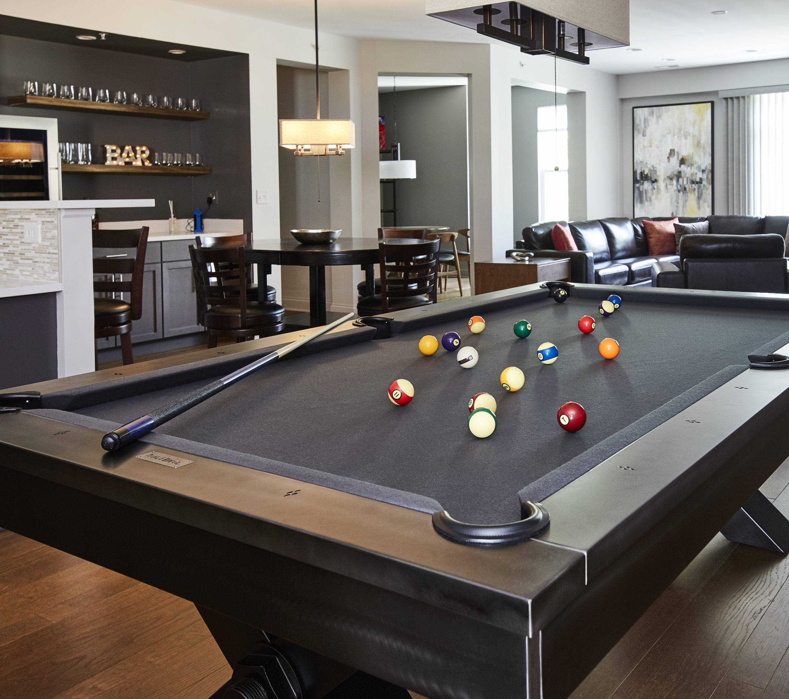 A pool table is prominently displayed with a home bar and leather sofa is featured in the background.